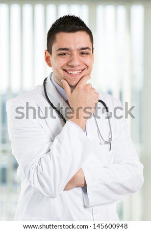 Handsome doctor smiling and looking at you.