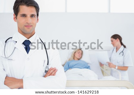 Handsome doctor with arms crossed in front of patient and doctor