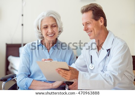 Handsome doctor with old patient