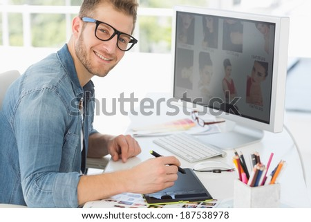 Handsome editor working with digitizer smiling at camera in creative office - stock photo