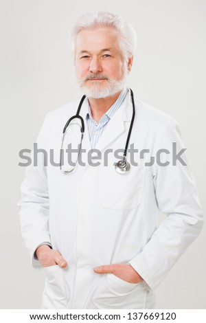 Handsome elderly doctor in uniform isolated over light background - stock photo
