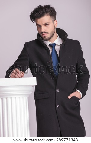 Handsome elegant business man holding one hand in his pocket while leaning his hand on a white column.