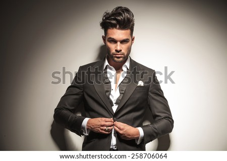 Handsome elegant business man looking at the camera while unbuttoning his jacket. - stock photo