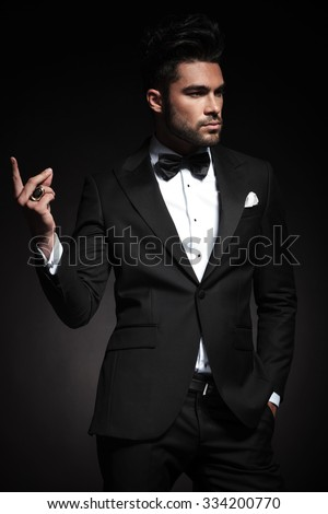 Handsome elegant business man looking away from the camera while snapping his fingers. - stock photo