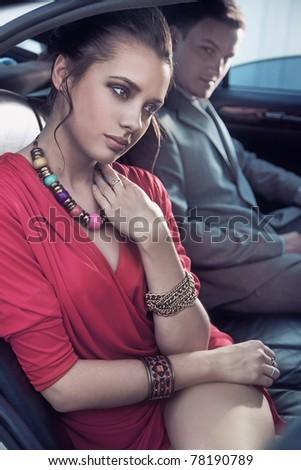 Handsome elegant couple traveling a luxury vehicle - stock photo