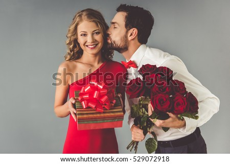 Handsome elegant guy in classic shirt with red bow tie is giving roses and gift box to his beautiful girlfriend and kissing her
