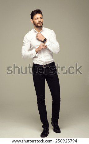 Handsome elegant man buttoning shirt - stock photo