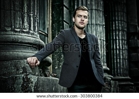 Handsome elegant man posing on a city street. Fashion shot. Business man outdoor. - stock photo