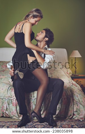 Handsome elegant man undressing woman. Sensuality and love - stock photo