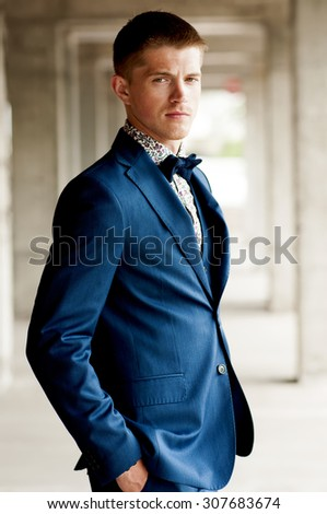 Handsome elegant man wears blue suit with bow tie outdoor. - stock photo