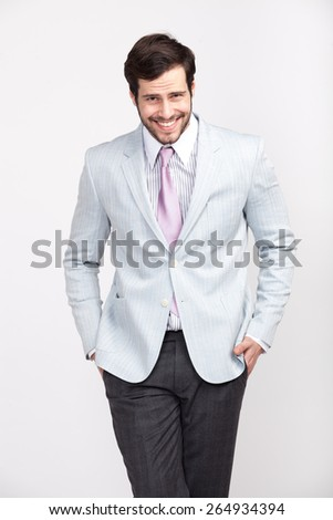 handsome elegant man with beard smiling, dressed in light-colored suit with attitude, isolated - stock photo