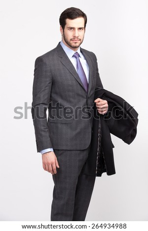 handsome elegant man with beard with overcoat in hand dressed in gray suit, isolated - stock photo