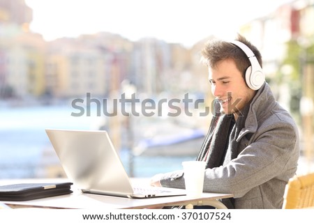 Handsome elegant man working with laptop and headphones watching a video lecture on line in a coffee shop terrace in winter - stock photo