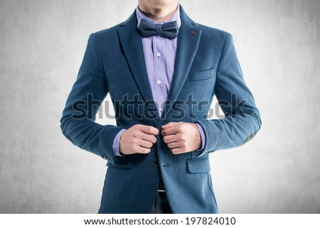 Handsome elegant young fashion man in coat tuxedo classical costume suit and bow tie - stock photo