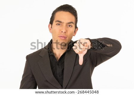 handsome elegant young latin man wearing a suit posing holding thumb down isolated on white