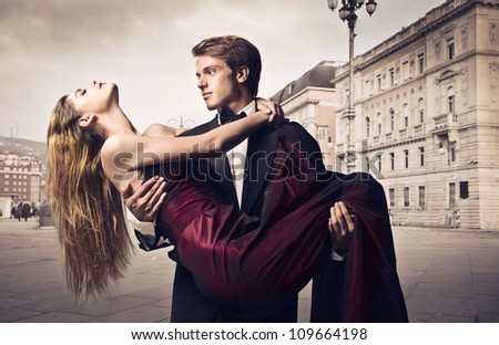 Handsome elegant young man holding his girlfriend in his arms with town square in the background - stock photo