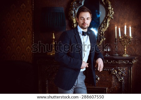 Handsome elegant young man in classic vintage apartments. Fashion. Luxury. - stock photo
