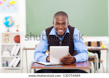 handsome elementary school teacher using a tablet computer - stock photo