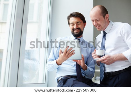 Handsome employee with touchpad explaining data to his colleague - stock photo