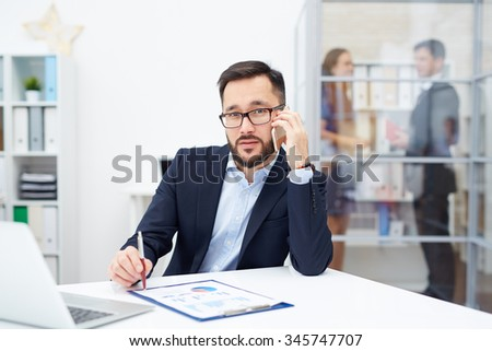 Handsome employer calling at workplace in office