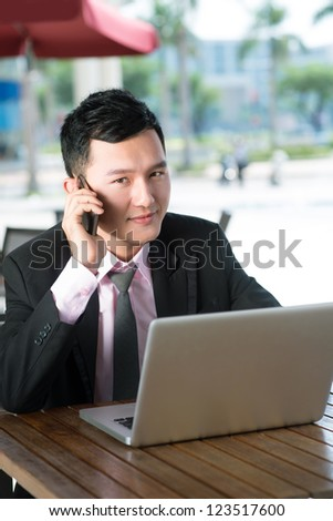 Handsome entrepreneur working on laptop consulting client by the phone - stock photo