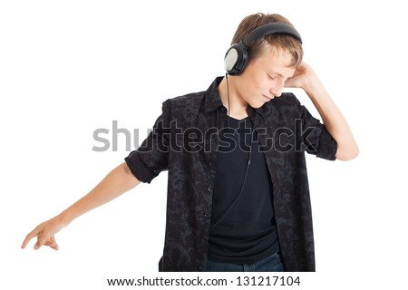 Handsome European teen boy wearing a black shirt with headphones. Boy listening to music with his eyes closed. Studio shot, isolated on white background. - stock photo
