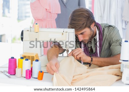 Handsome fashion designer sewing with a sewing machine - stock photo