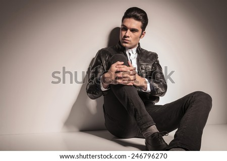 Handsome fashion man looking to his side while sitting on the floor and holding his leg with both hands. - stock photo