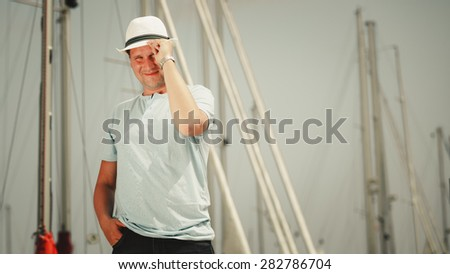 Handsome fashion man tourist on pier in port with yachts. Guy enjoying summer travel vacation by sea.