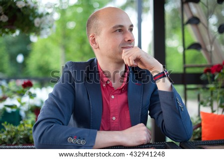 handsome fashionable bald man thinking. outdoors portrait - stock photo