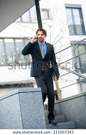 Handsome fashionable businessman listening to a call on his mobile smiling as he looks thoughtfully off to the side as he walks along outdoors