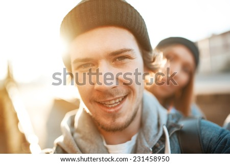 Handsome fashionable guy photographing himself with a girl on the street on a sunny day - stock photo