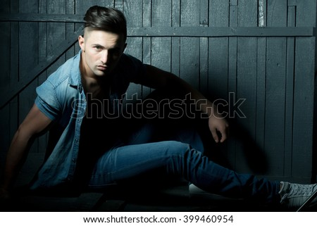 Handsome fashionable sexy sensual muscular young macho man with bare torso and stylish hair in jeans shirt indoor sitting on wooden background, horizontal picture - stock photo