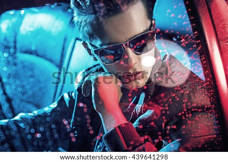 Handsome fashionable yonug man sitting in a car - stock photo