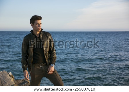Handsome fashionable young man at the seaside along the shore overlooking the ocean or sea with his black leather jacket looking far away, large copyspace - stock photo