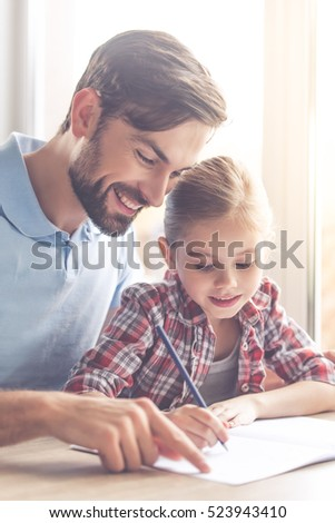 Handsome father and his cute little daughter are drawing and smiling while spending time together