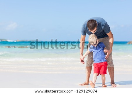 handsome father and his son at the caribbean beach - stock photo