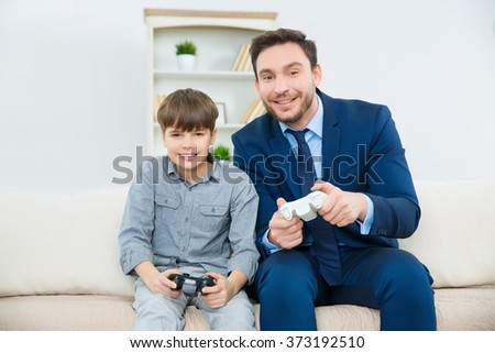Handsome father enjoys playing video games with adorable son - stock photo