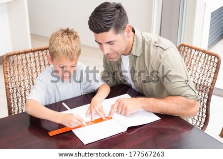 Handsome father helping son with homework at table at home in kitchen