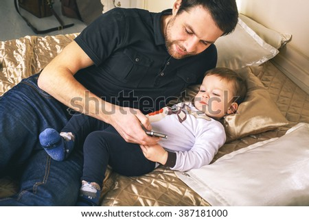 Handsome father playing with his little son at home