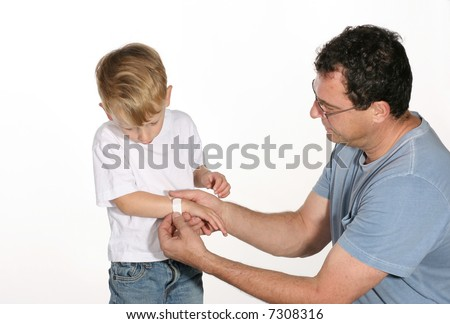 Handsome father putting a band aid on his son's arm - stock photo