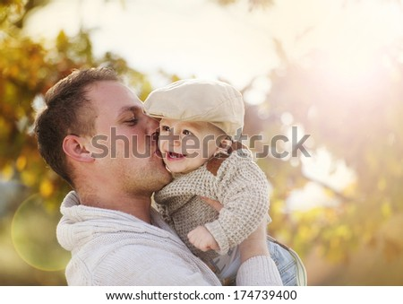 Handsome father relaxing with his son in colorful autumn nature - stock photo