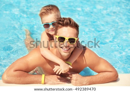Handsome father with little son in swimming pool at water park