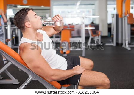 Handsome fit athlete is drinking water with enjoyment. He is sitting on bench and resting in gym. The man closed his eyes with relaxation - stock photo