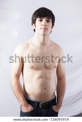 Handsome fit male standing with his shirt off, his muscles   well defined, his hands in his pockets, Looking at the camera with a serious, focused expression - stock photo
