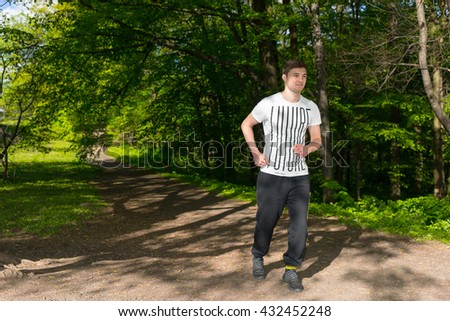 Handsome Fit Man Athlete Running At Speed Along A Rural Lane Through The Park
