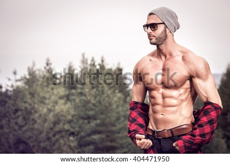 Handsome fit man posing outdoors in forest wearing checked shirt - stock photo