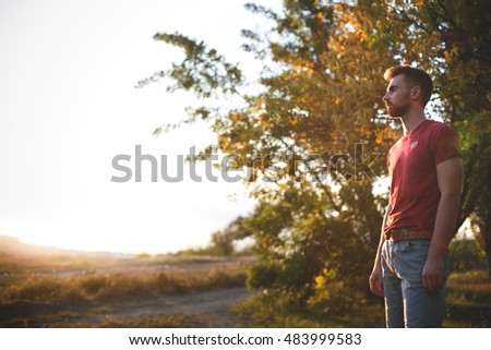 Handsome fit man posing outdoors in forest wearing red t-shirt
