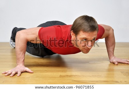 Handsome fit man pursuing a healthy lifestyle, doing push-up fitness exercise in the gym - stock photo