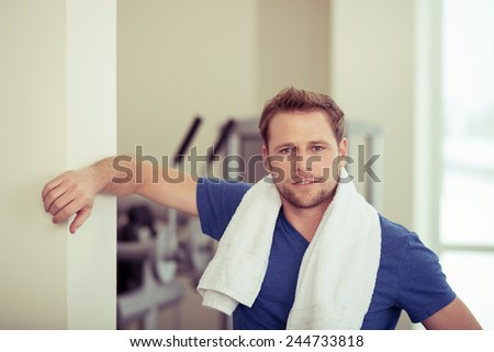 Handsome fit young man in a gym posing leaning against a wall with a towel around his neck looking at the camera - stock photo